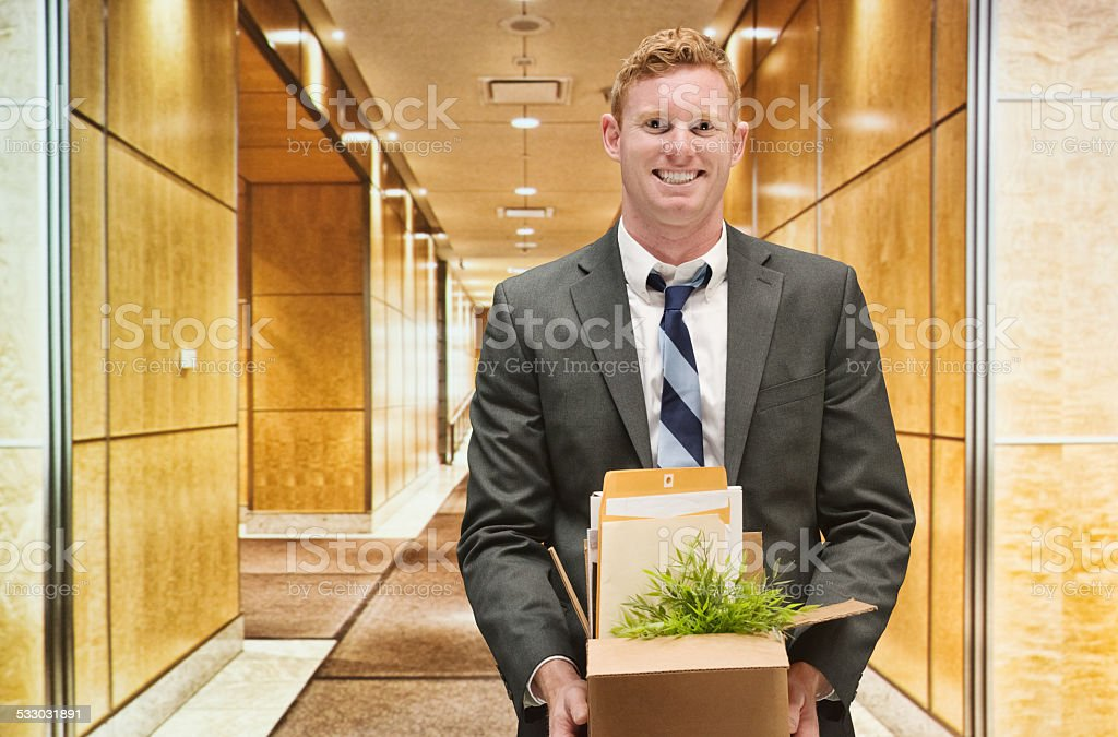 Cheerful businessman holding box in...