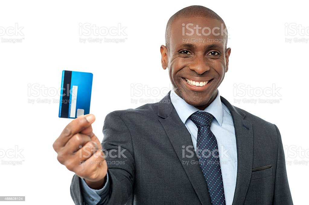 Cheerful businessman holding credit card stock photo