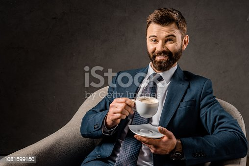 1081599130 istock photo cheerful businessman holding cup of coffee and sitting in armchair 1081599150
