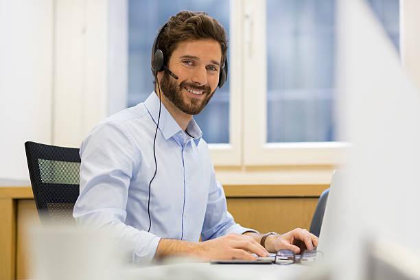 alegre empresário no escritório com telefone, auscultadores com microfone, skype - skype imagens e fotografias de stock