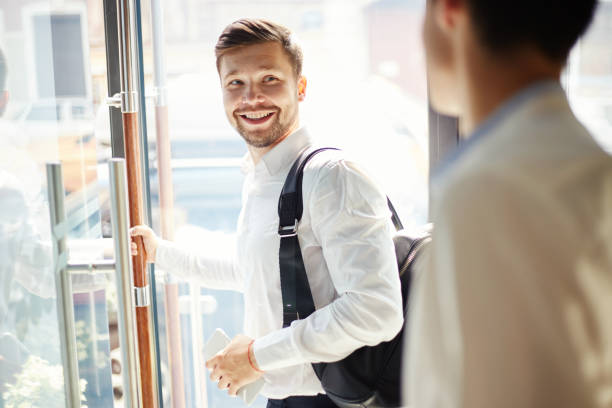 Cheerful businessman leaving cafe and smiling Young elegant man with trendy backpack walking out of cafe door and smiling over back saying goodbye apart stock pictures, royalty-free photos & images
