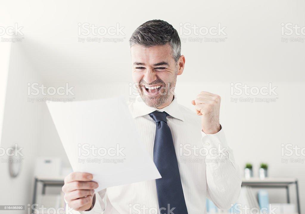 Cheerful businessman receiving good news stock photo