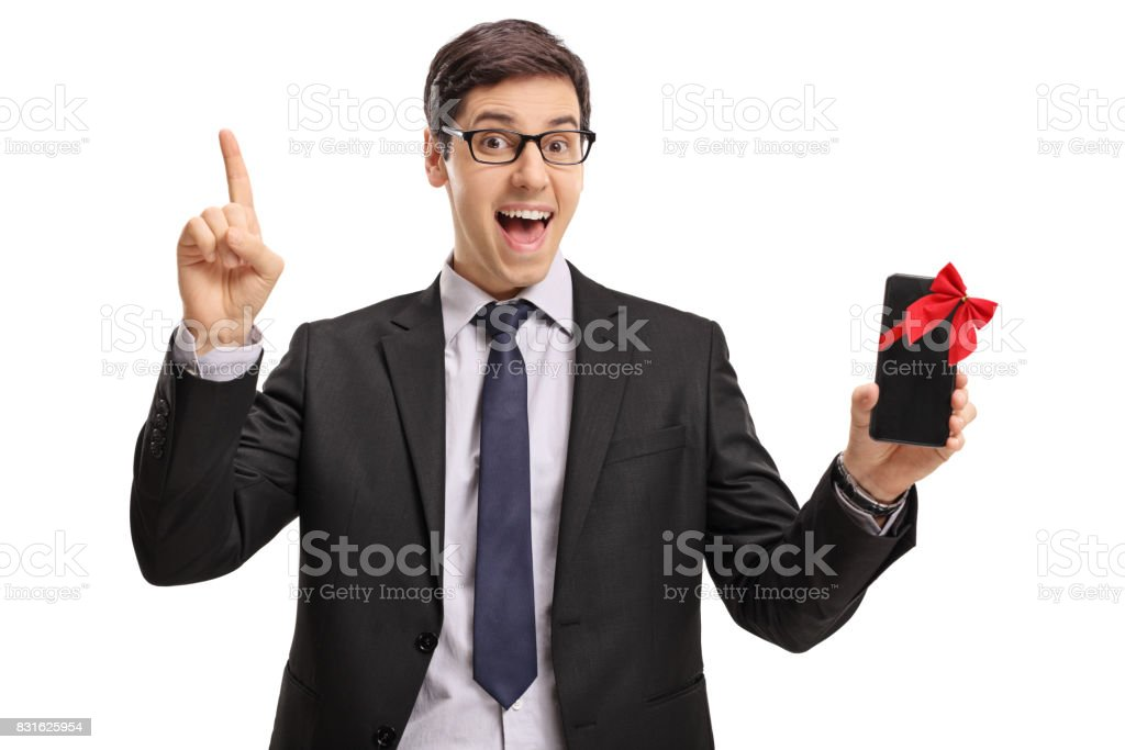 Cheerful businessman showing a phone and pointing up stock photo