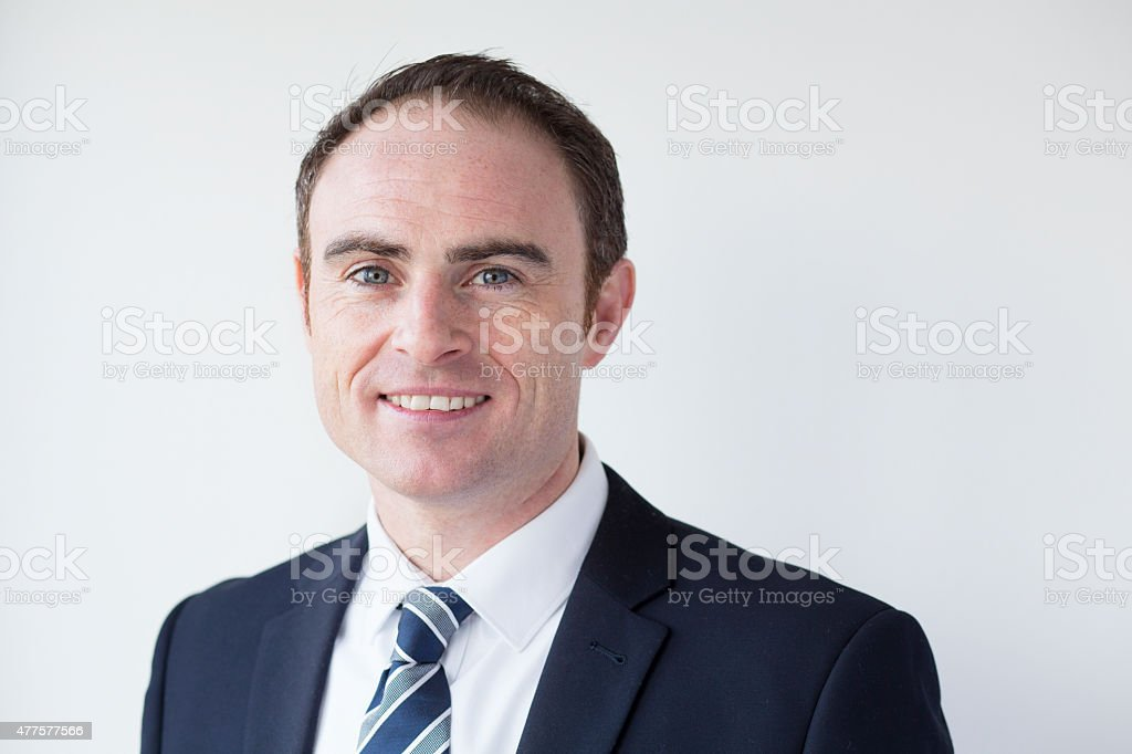 Cheerful Businessman Smiling at Camera with Plain Wall Behind. stock photo