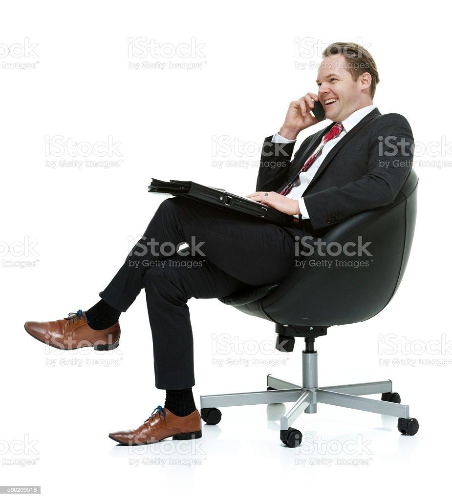 Cheerful businessman talking on phone royaltyfri bildbanksbilder