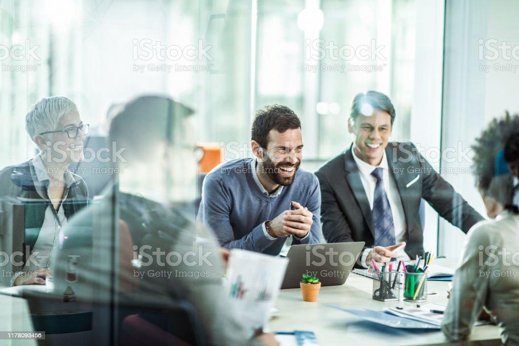 Fröhlicher Geschäftsmann im Gespräch mit seinen Kollegen im Büro. - Lizenzfrei Zusammenarbeit Stock-Foto