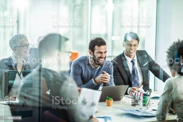 Fröhlicher Geschäftsmann Im Gespräch Mit Seinen Kollegen Im Büro Stockfoto und mehr Bilder von Zusammenarbeit