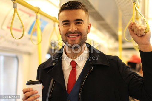 Cheerful businessman using public transportation.
