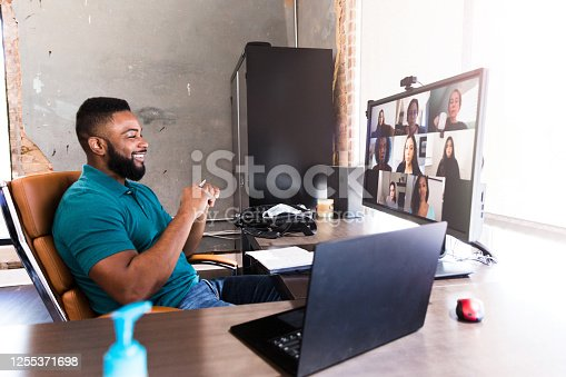 A mid adult businessman smiles confidently as he talks with a team of associates during a virtual meeting during the COVID-19 pandemic.
