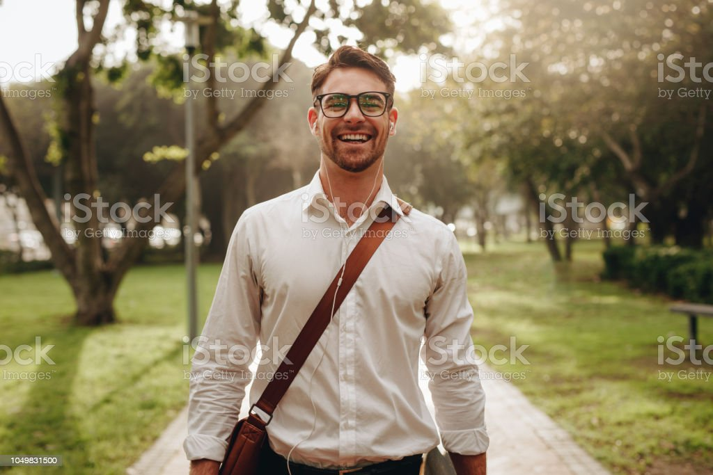 Cheerful businessman walking through a park going to office stock photo