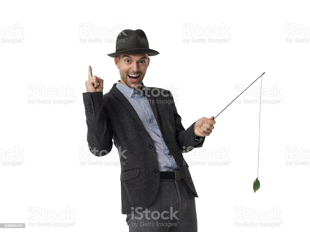 Cheerful businessman wearing hat and fishing stock photo
