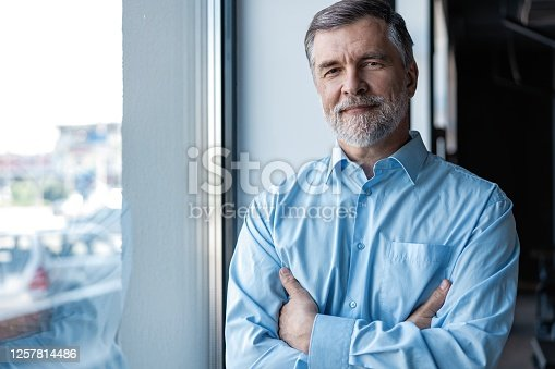 cheerful businessman with arms folded looking at the camera while standing near the window in office building