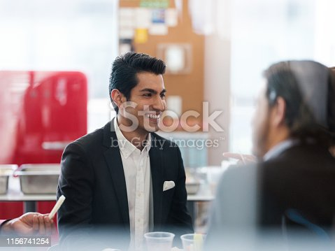 A photo through a glass door of a cheerful businessman with a toothy smile sitting in front of colleagues.