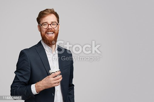 Attractive ginger bearded male with cup of fresh hot drink smiling and looking at camera while standing against gray background during break