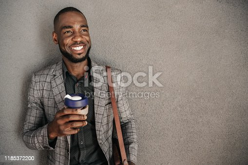 Portrait of young African businessman holding reusable cup of coffee.