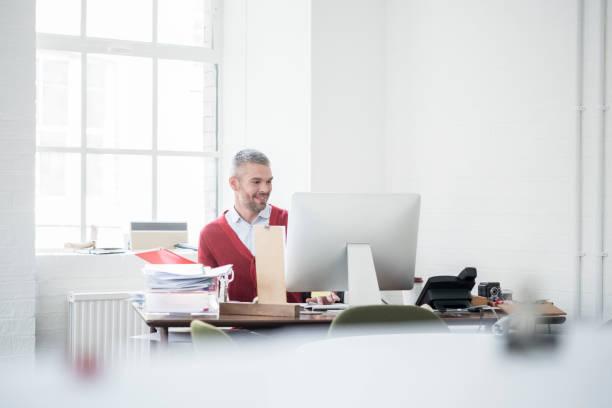 Cheerful businessman with grey hair and beard sitting at desk using picture id949500874?b=1&k=6&m=949500874&s=612x612&w=0&h=uem4i9orkxpzrbbi5wpvrtuiy1t akk5dkf4sq7lt4m=