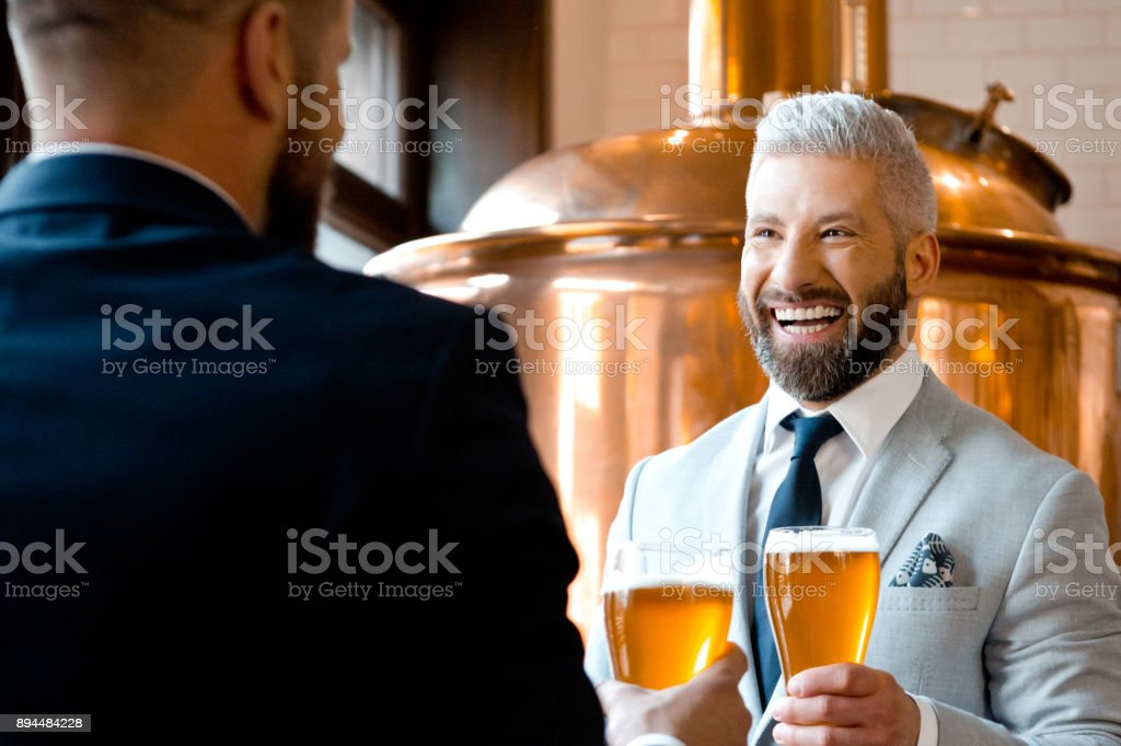 Cheerful businessmen talking over beer in the microbrewery Two businessmen laughing and talking over beer in the microbrewery. Mature businessman smiling while talking with his partner holding beer glass. Adult Stock Photo