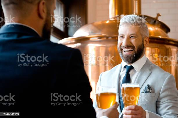 Cheerful Businessmen Talking Over Beer In The Microbrewery Stock Photo - Download Image Now