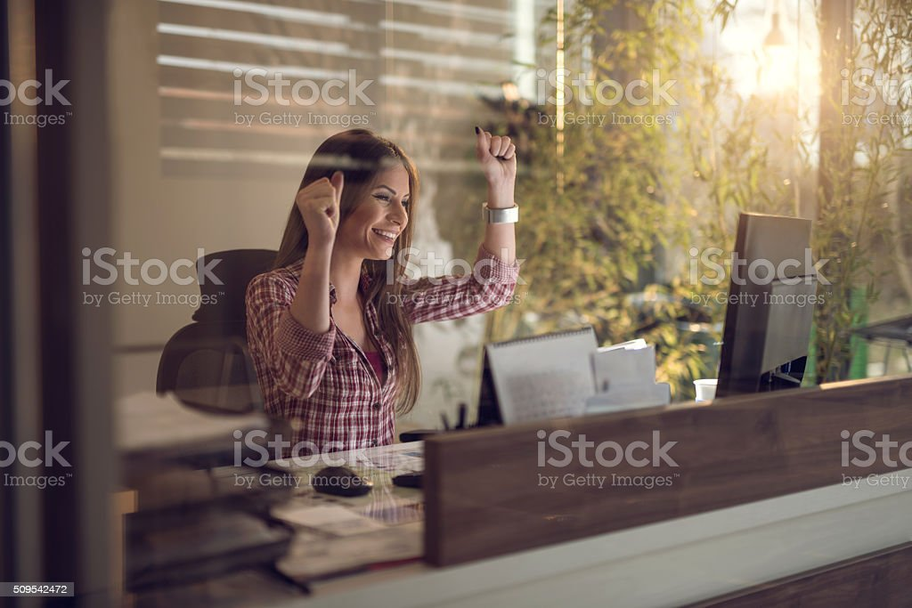 Cheerful businesswoman celebrating success in the office. stock photo