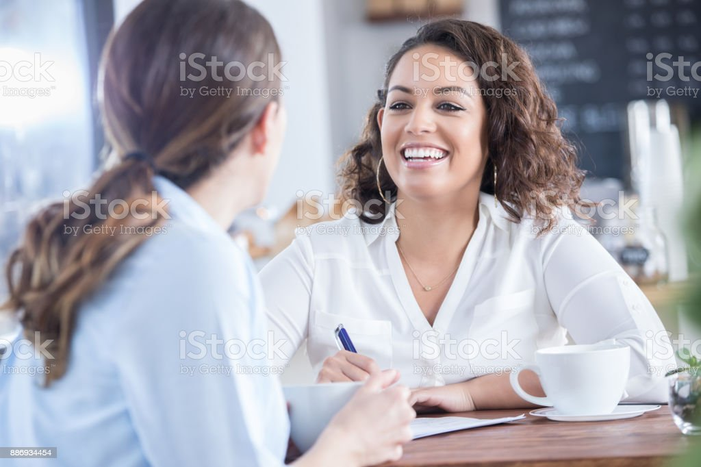 Cheerful businesswoman discusses resume with interviewee A cheerful businesswoman listens to an unrecognizable interviewee as she sits across from her at a table in a coffee shop and discusses her resume. Adult Stock Photo