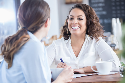 Cheerful Businesswoman Discusses Resume With Interviewee Stock Photo - Download Image Now