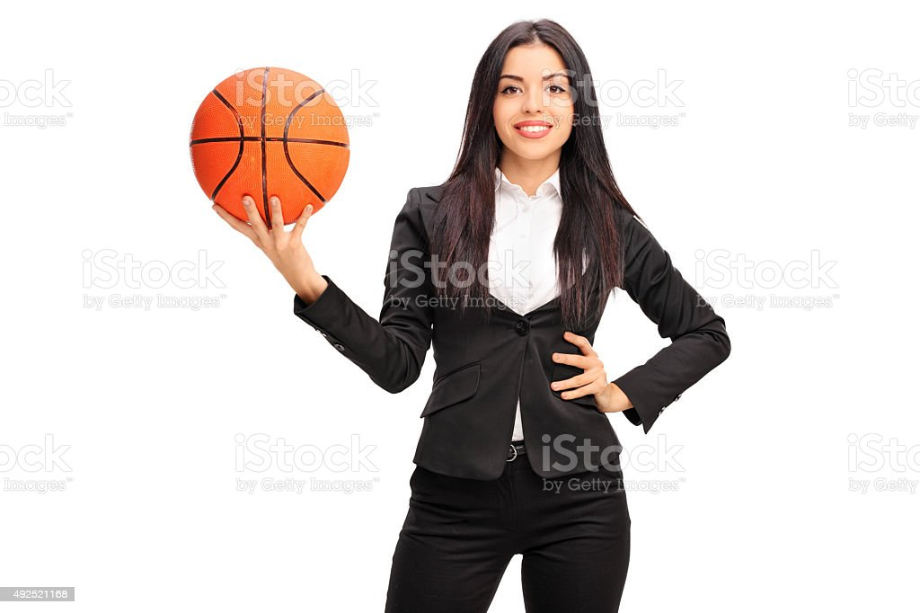 Cheerful businesswoman holding a basketball stock photo