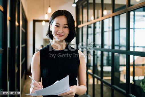Waist up shot of beautiful professional woman smiling towards camera in office corridor, elegance, intelligence, working