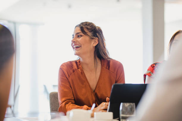Cheerful businesswoman laughing at conference table stock photo