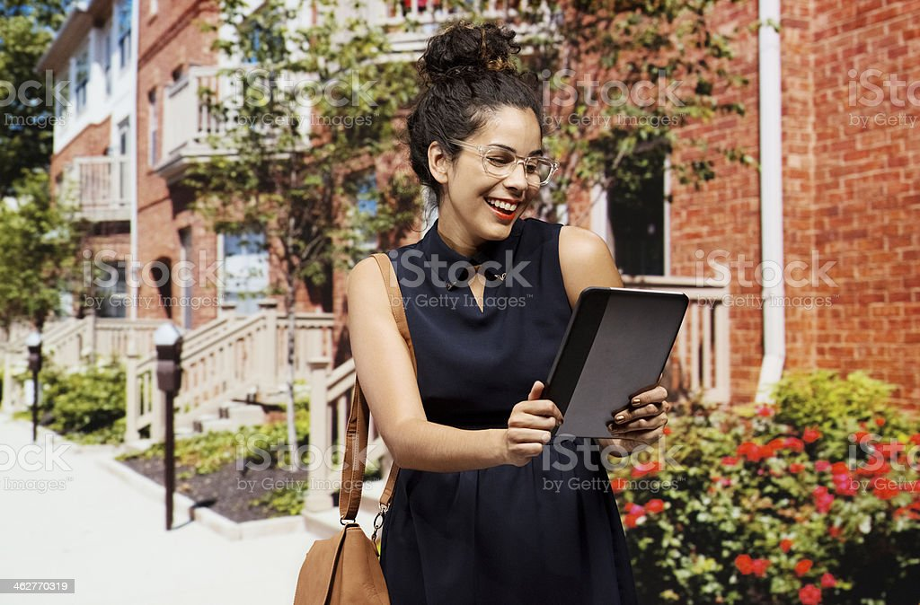 Cheerful businesswoman looking at tablet royalty-free stock photo