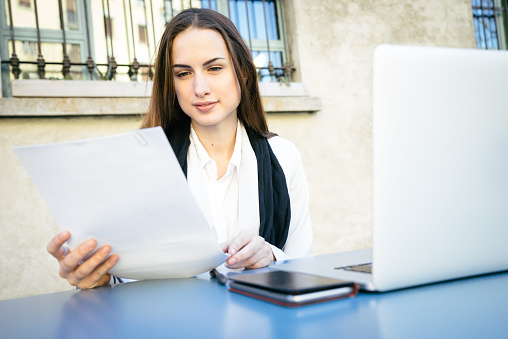istock Cheerful Businesswoman Reading Documents 468386172