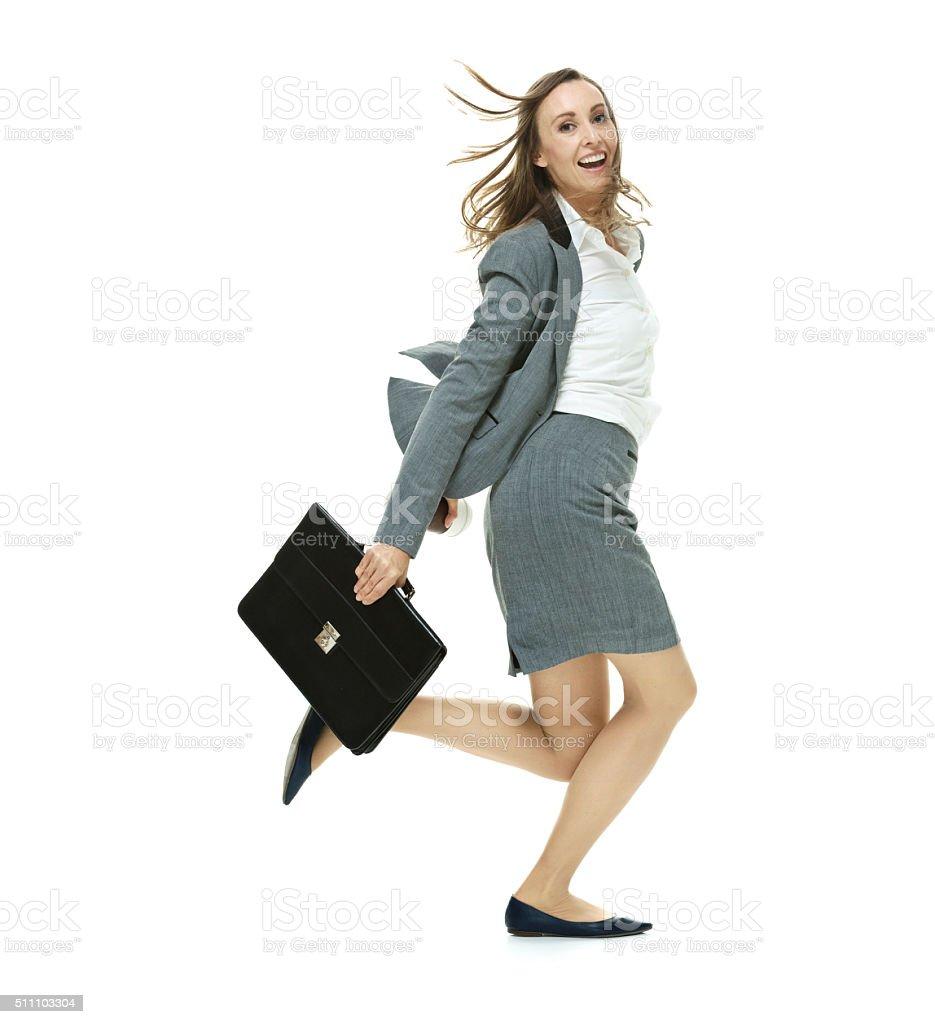 Cheerful businesswoman running stock photo