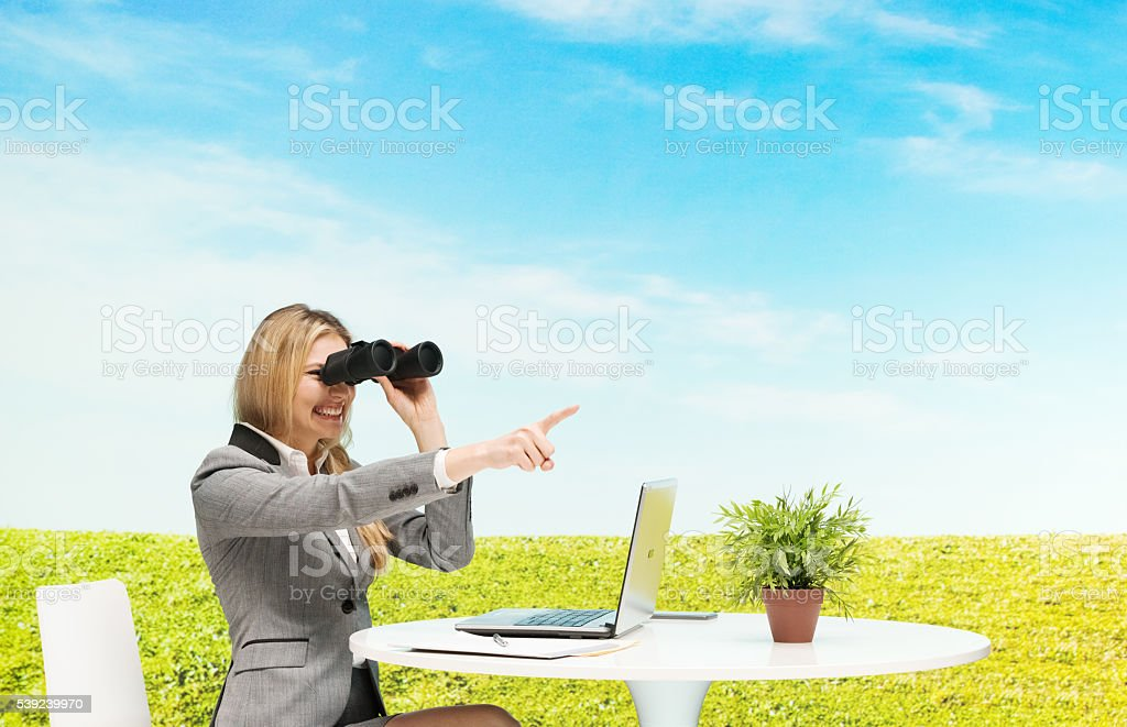 Cheerful businesswoman searching with binoculars royalty-free stock photo