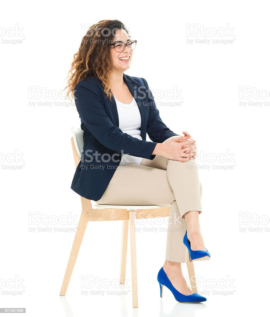 Cheerful businesswoman sitting on chair stock photo