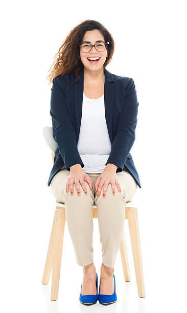 Cheerful businesswoman sitting on chair stock photo