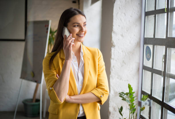 Cheerful businesswoman standing at her office and talking on the mobile phone stock photo