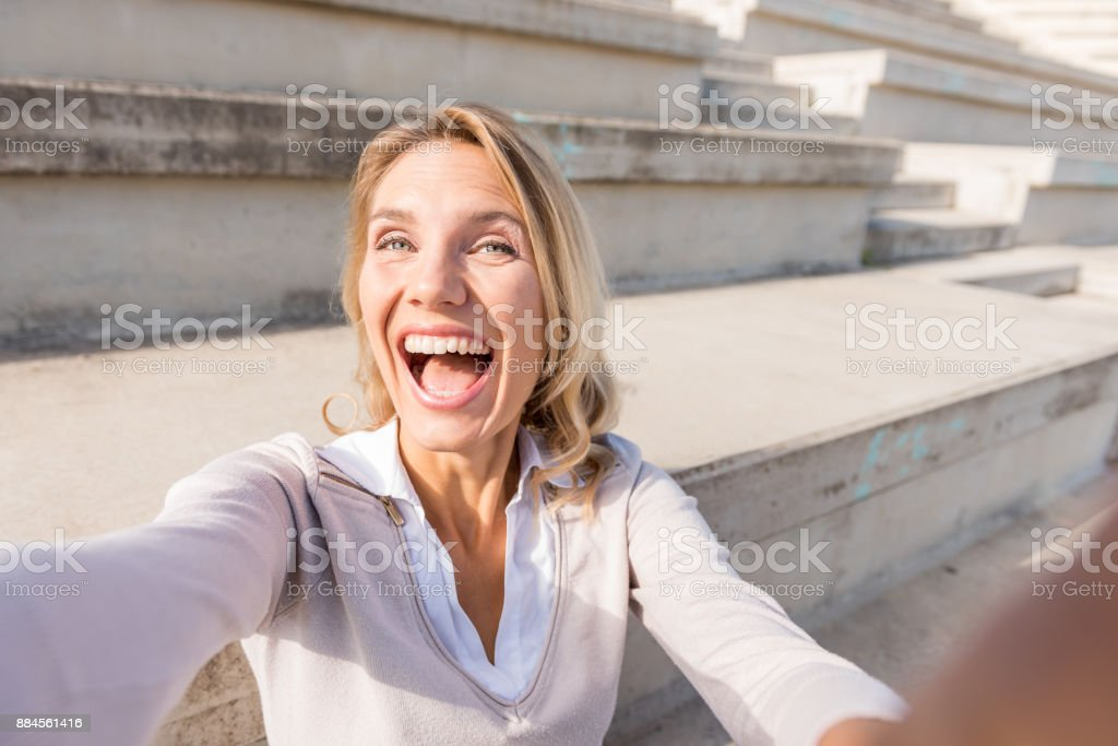 Cheerful businesswoman taking selfie on steps stock photo