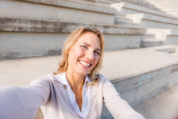 Cheerful businesswoman taking selfie on steps