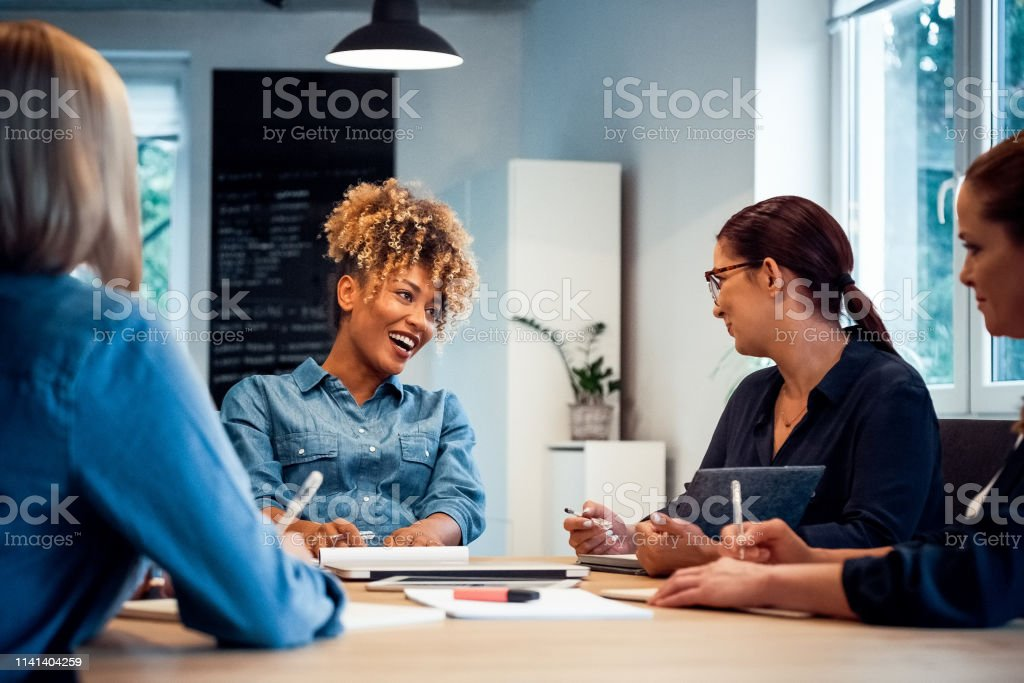 Cheerful businesswoman talking to colleagues Cheerful pregnant businesswoman talking with colleagues at desk. Female professionals are working in new office. They are discussing start-up project. 35-39 Years Stock Photo
