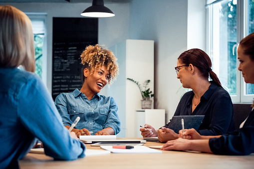 Cheerful Businesswoman Talking To Colleagues Stock Photo - Download Image Now
