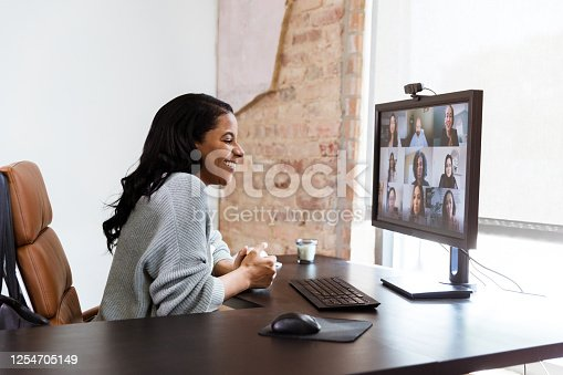 Cheerful businesswoman laughs while participating in a virtual staff meeting. The woman is using a desktop pc in her office to access the virtual meeting.