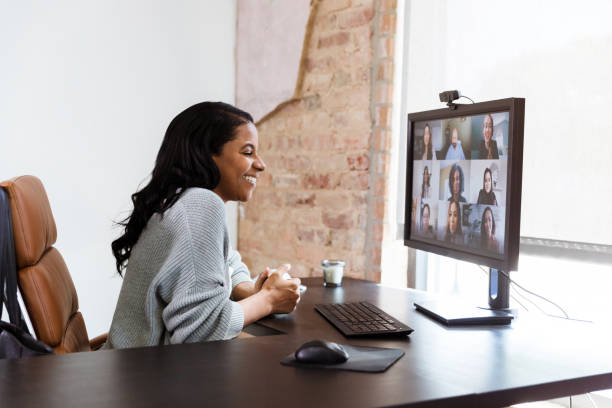 Cheerful businesswoman talks with colleagues during video call stock photo