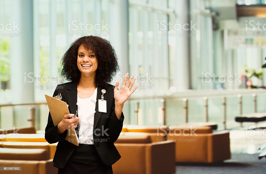 Cheerful businesswoman waving hand stock photo