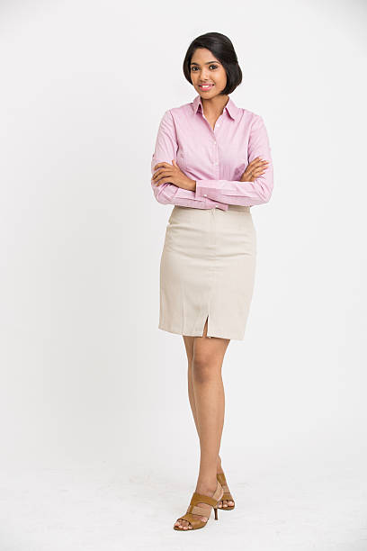 cheerful businesswoman with her arms crossed standing stock photo