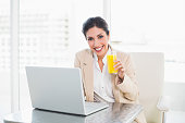 Cheerful businesswoman with laptop and glass of orange juice at desk at the office
