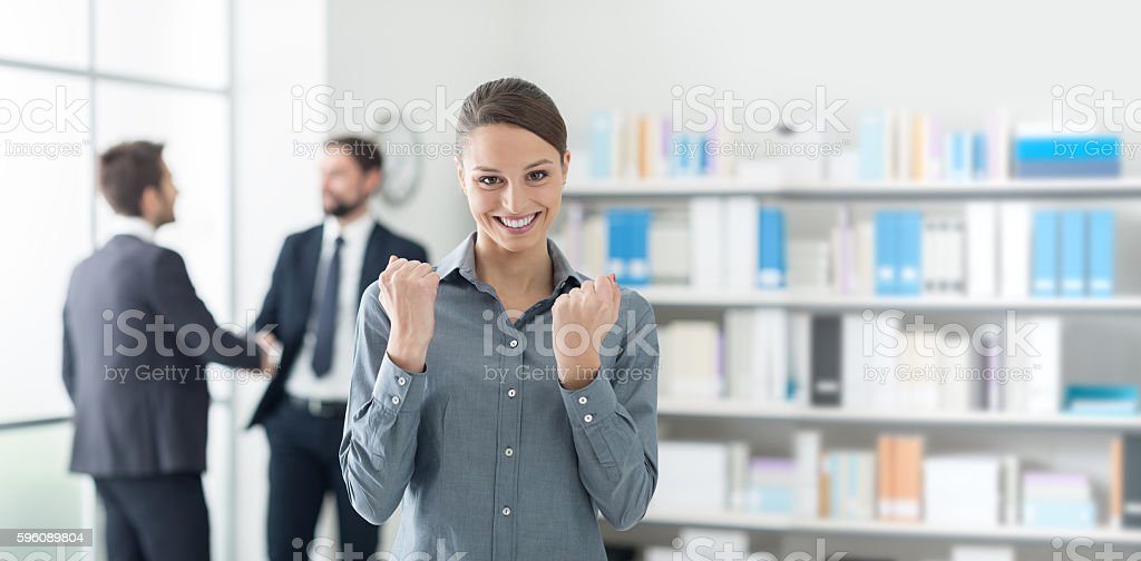Cheerful businesswoman with raised fists royalty-free stock photo