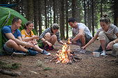 Cheerful hiking group enjoying their day in a mountain forest, camping.