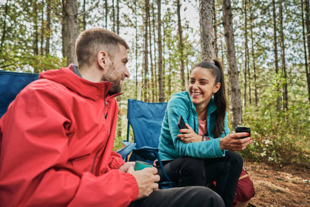 Cheerful camping couple enjoying talking and tea in the forest Handsome, cheerful and carefree young female and male hiking couple enjoying camping in the mountains in autumn. image stock pictures, royalty-free photos & images