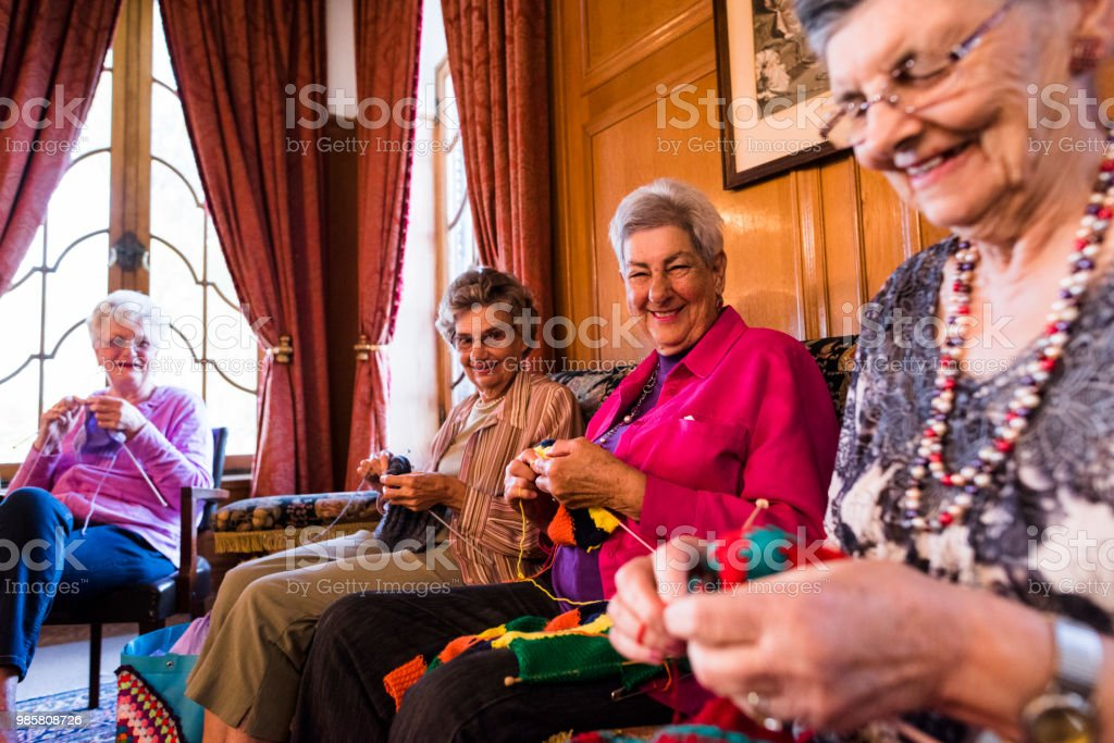 Cheerful candid portrait of senior women knitting stock photo