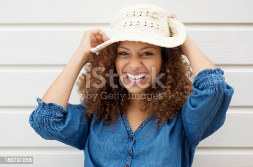 186534921 istock photo Cheerful carefree woman laughing and wearing summer hat 186292658