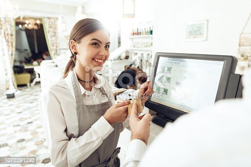 istock Cheerful cashier using digital device for payment 1072291292